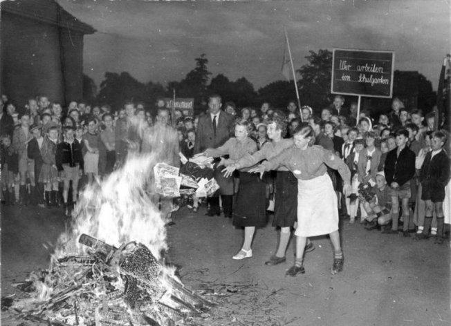 """Bücherverbrennung anno 1955: Die Schülerinnen, Schüler und Jungen Pioniere der 18. Grundschule in Berlin-Pankow (Buchholz) werfen am Abend des Internationalen Kindertages 1955 """"Schmutz- und Schundliteratur"""" auf den Scheiterhaufen. Sie gaben damit den Auftakt für eine Welle von Elternversammlungen, in denen ein Verbot der Schund- und Schmutzliteratur für das Gebiet der DDR und Groß-Berlin durch ein Gesetz gefordert wurde."""